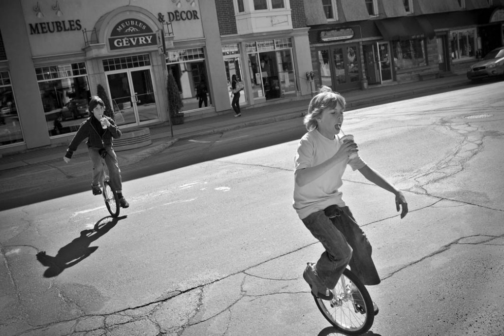two boys drink their sodas and unicycle across a main street in Sherbrooke, QC