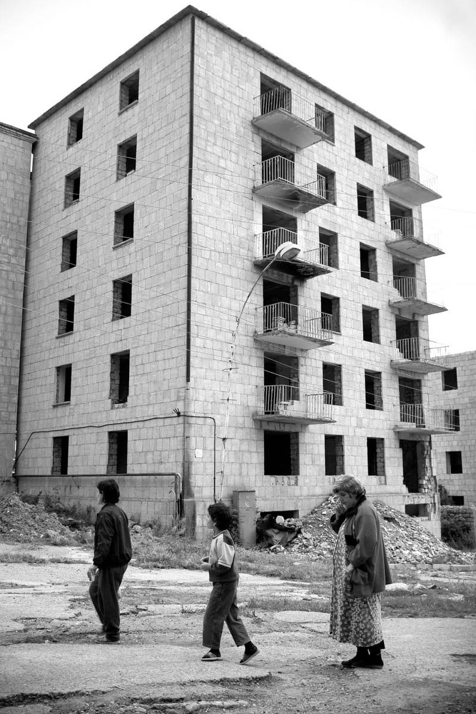 Residents walk past bombed out buildings from the Armenian Azeri war in Shushi, Nagorno Karabakh.