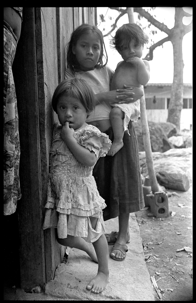 9 year old Helen holds baby brother Jason, 1, with younger sister Maylin, 7, on San Antonio farm in the municipality of La Dalia, Matagalpa, Nicaragua. Helen will take care of her siblings, untill she is old enough to join her parents picking coffee.