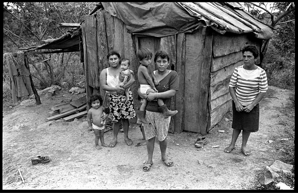 "Gloria Cruz Hernandez, Cecilia Sanchez Alarcon and Esmeralda Montoya Perez, Matagalpa , Nicaragua. All they own is a little home like the one behind them. These ladies had taken part in the ""plantones"" (unemployed coffee workers had lined alongside highways, and gathered public squares ). Government had promised some land to workers who would return to work for aproximately 2 US $/day. But 6 months later they had still not received any land nor any of the health or education centers that were promised."