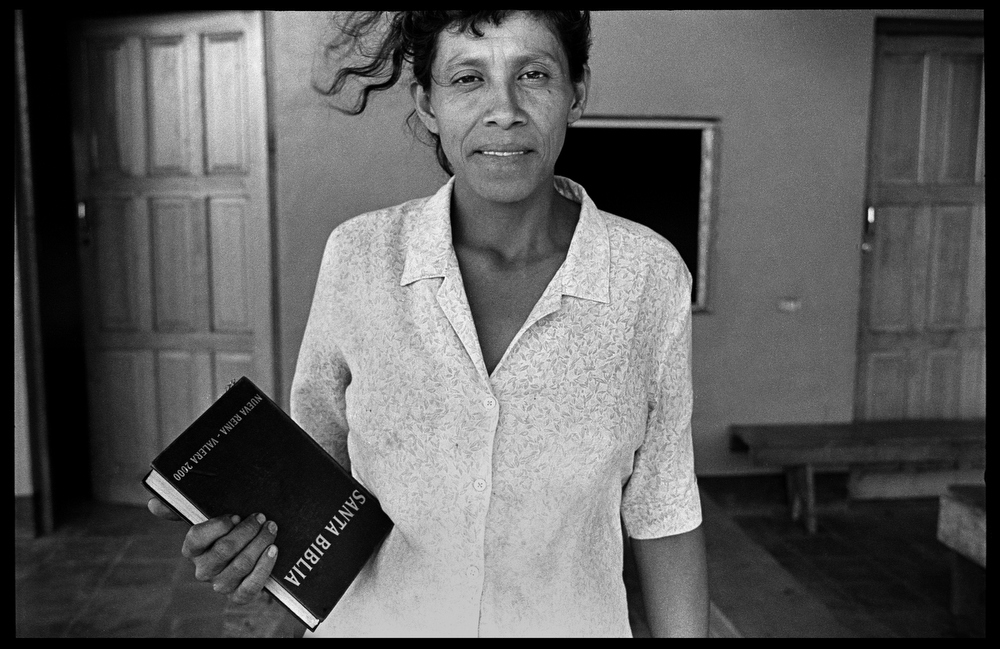 A woman on La Golondrina farm finds solace in her bible. She is pictured here in front of the recently built evangelical church on the plantation. Religion plays an important role for many coffee workers.