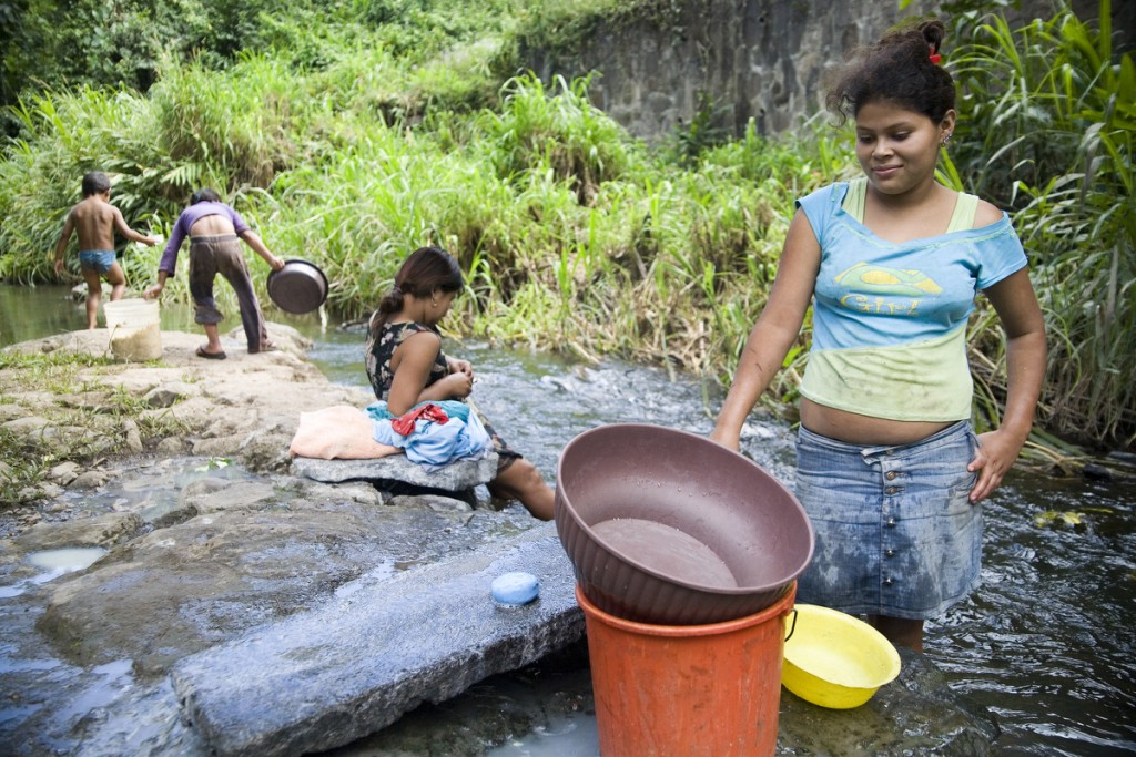Women do laundry in the river running through La Corona community.