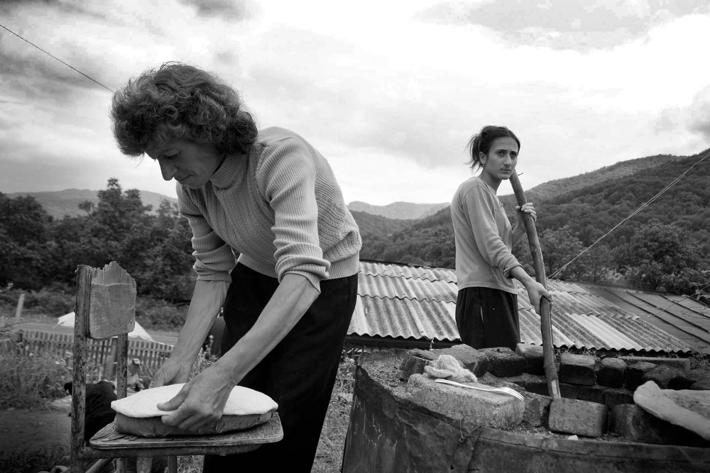 Mother and daughter bake traditional flat bread on the road between Stepanakert and Gandazar.