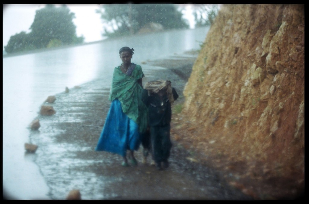 A women and children make their way home during a rain storm